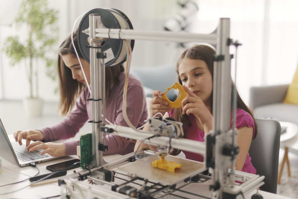 Young girls learning to use 3D printer at home